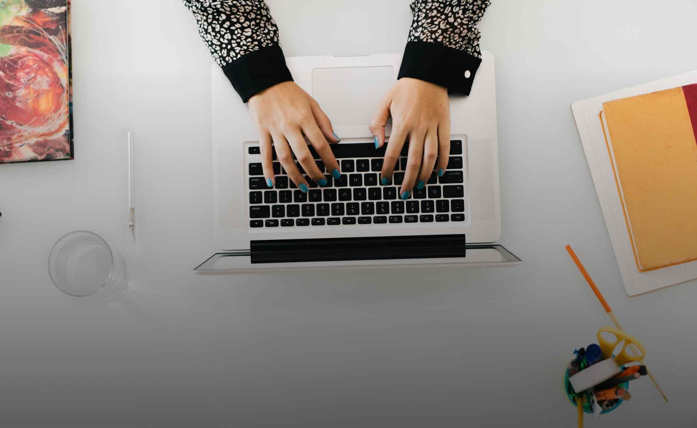 Sicht von oben auf einen Schreibtisch, Hände bedienen einen Laptop.