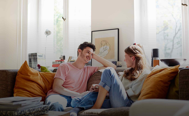 Ein Mann und eine Frau sitzen auf einem Sofa und unterhalten sich