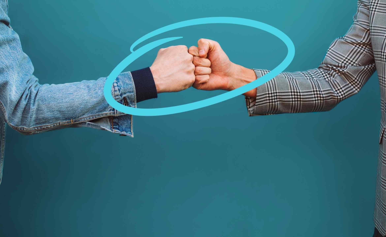 Zwei Fäuste, die sich berühren und ein freundschaftliches Zusammenarbeiten symbolisieren
